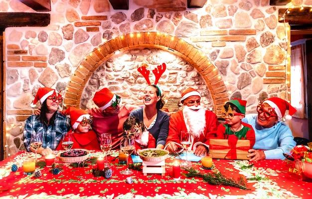 Famille multigénérationnelle sur les vêtements du père noël s'amusant à la fête de noël à la maison