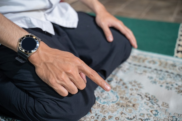 Famille musulmane asiatique priant jamaah ensemble à la maison. sholat ou salah vêtu de blanc et de hijab