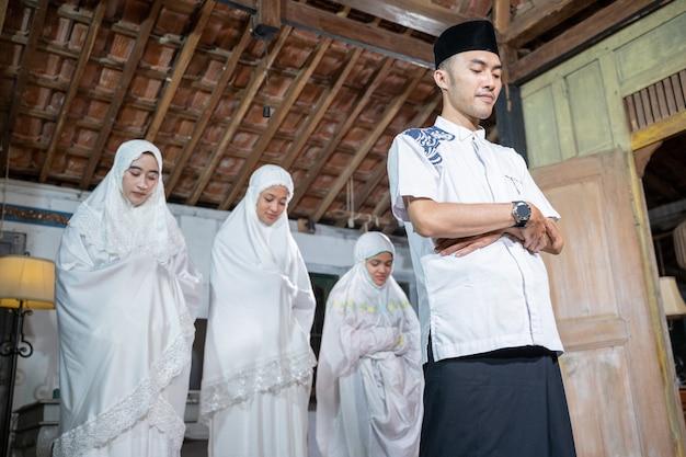 Famille musulmane asiatique priant jamaah ensemble à la maison