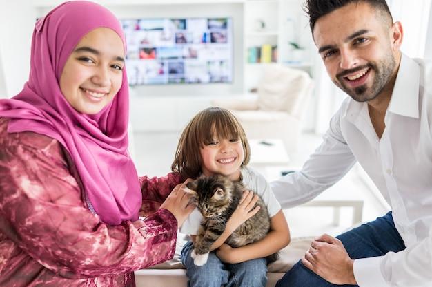 Famille musulmane à la maison moderne s'amuser et passer du bon temps avec chat animal de compagnie