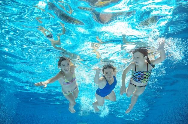 Famille nage dans la piscine sous l'eau, heureuse mère active et les enfants s'amusent sous l'eau, fitness et sport avec les enfants en vacances d'été sur la station