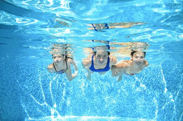 La famille nage dans la piscine sous l'eau, la mère active heureuse et les enfants s'amusent sous l'eau, le fitness et le sport avec les enfants en vacances d'été sur la station