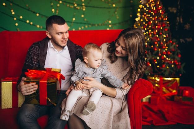 Famille à noël assis sur un canapé rouge par l'arbre de noël