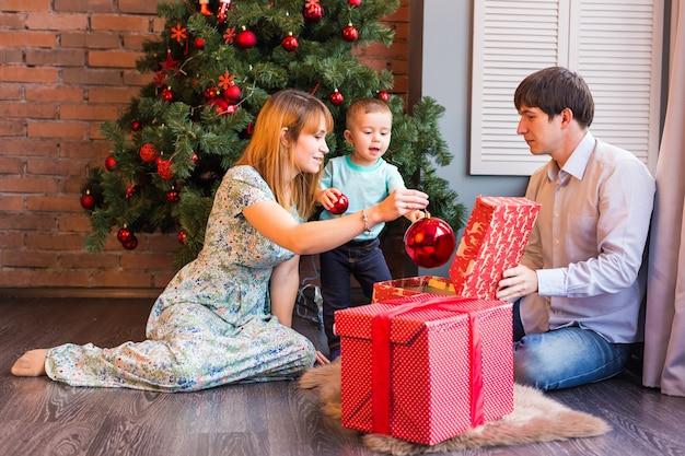 Famille de noël avec bébé. cadeau d'ouverture de l'enfant heureux. sapin de noël