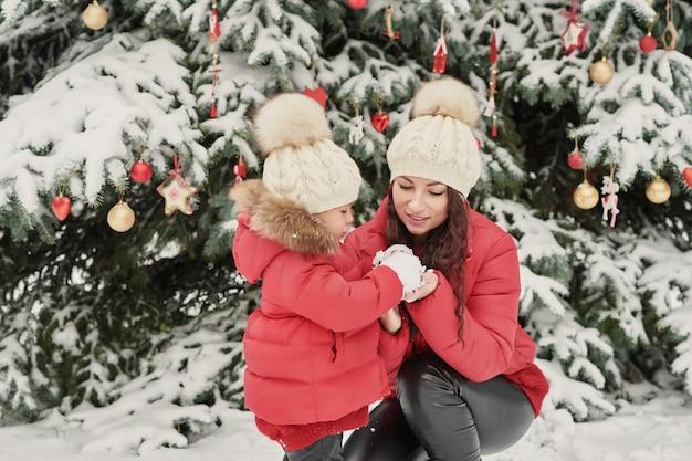 Famille de noël à winter park. heureuse mère de famille et fille enfant s'amuser, jouer à la promenade d'hiver à l'extérieur. plaisir en famille en plein air pendant les vacances de noël.vêtements d'hiver pour bébé et enfant en bas âge.