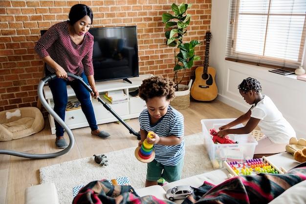 Famille noire nettoyant la maison ensemble