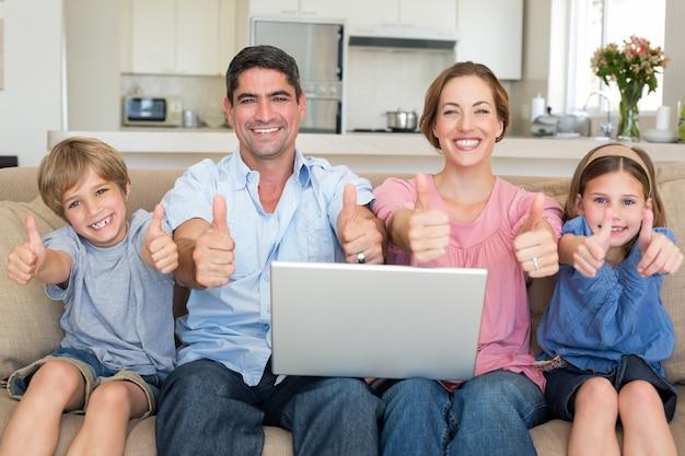 Famille avec ordinateur portable gesticulant pouce en l'air sur le canapé