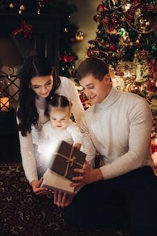 Famille ouvrant le cadeau de noël ensemble. chambre décorée pour noël.