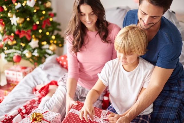 Famille ouvrant des cadeaux de noël dans le lit