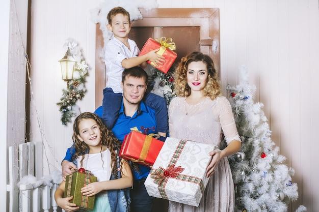 Famille, papa, maman et enfants heureux avec de beaux sourires pour fêter noël ensemble à la maison