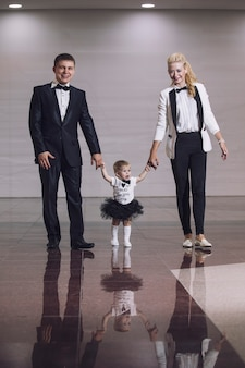 Famille, papa, maman et fille élégantes et habillées à la mode, belles et heureuses ensemble