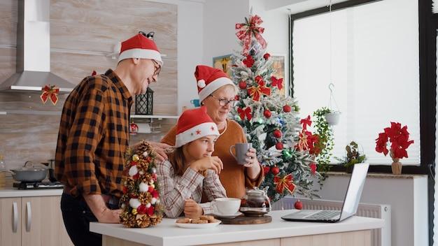 Famille parlant avec des parents distants lors d'une réunion par vidéoconférence en ligne sur un ordinateur portable