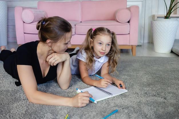 Famille passer du temps ensemble à la maison. maman avec sa fille dessine sur le sol. contrôle parental, mode de vie et concept d'enfants.