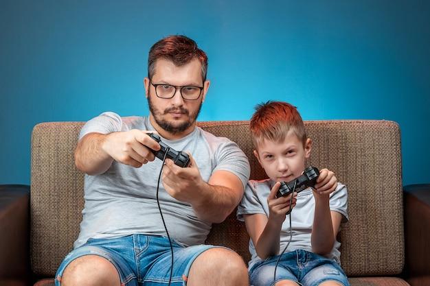 Une famille, un père et un fils joyeux jouent sur la console, dans les jeux vidéo, réagissent émotionnellement lorsqu'ils sont assis sur le canapé. jour de congé, divertissement, loisirs, passer du temps ensemble.