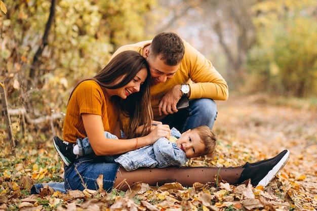 Famille avec un petit fils en automne parc