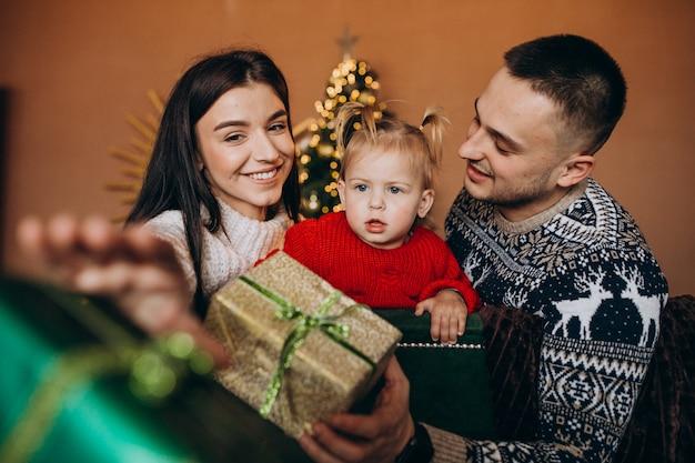 Famille avec petite fille assise devant un arbre de noël et une boîte-cadeau déballée