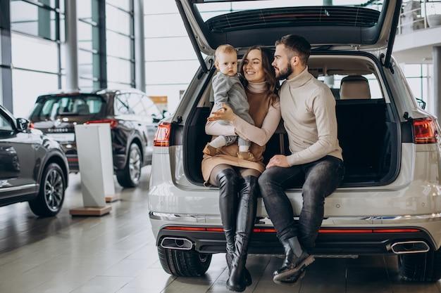 Famille avec petite fille choisissant une voiture dans une salle d'exposition automobile