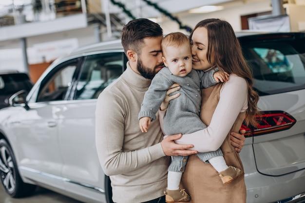 Famille avec petite fille choisissant une voiture dans un salon de l'automobile