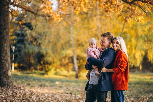 Famille avec petite fille marchant dans un parc en automne