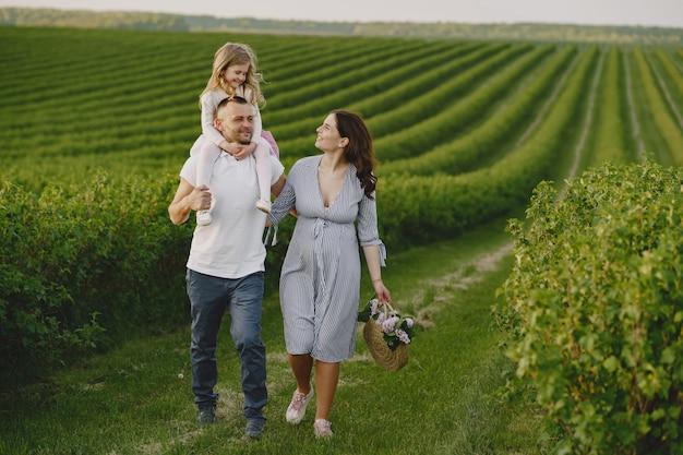 Famille avec petite fille, passer du temps ensemble dans un champ ensoleillé