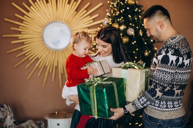 Famille avec petite fille près de boîte de cadeau de déballage d'arbre de noël