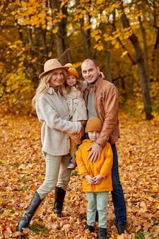 Famille avec petits enfants dans le parc d'automne aux beaux jours, portrait de famille caucasienne heureuse en marchant