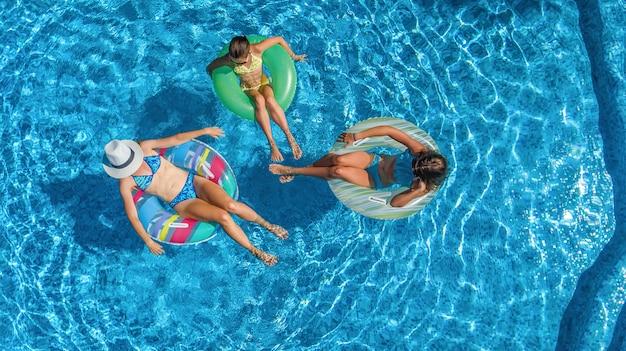 Famille en piscine drone aérien vue d'en haut, heureuse mère et enfants nagent sur des anneaux gonflables et amusez-vous dans l'eau en vacances en famille, vacances tropicales sur la station