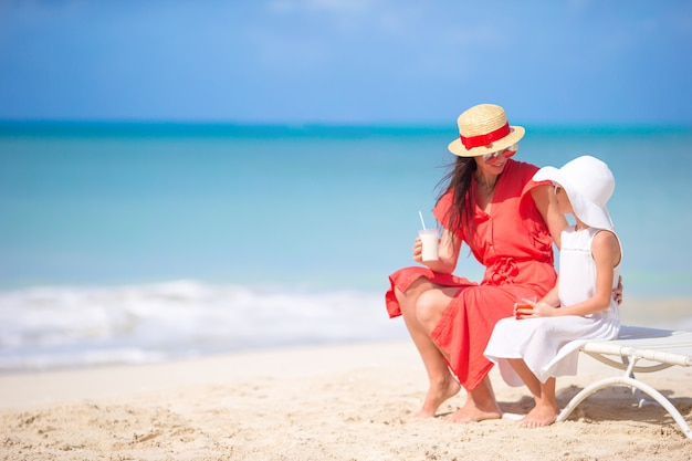 Famille sur la plage assis sur les chaises de plage