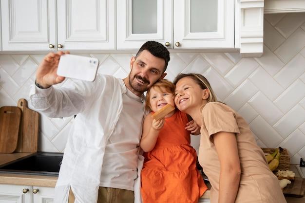 Famille de plan moyen prenant selfie