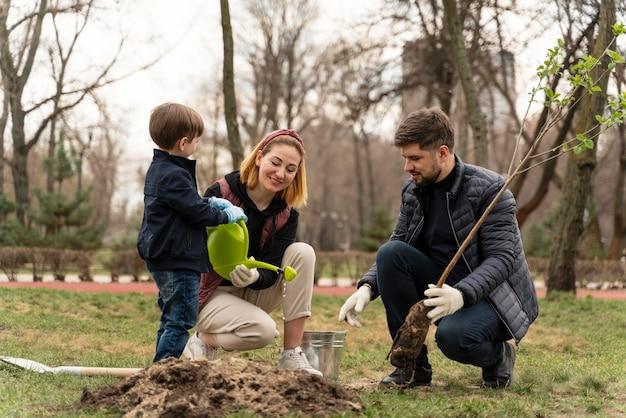 Famille plantant ensemble à l'extérieur
