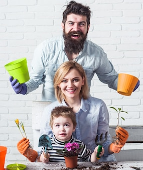 Famille plantant des fleurs ensemble. soin des plantes. notion de jardinage.