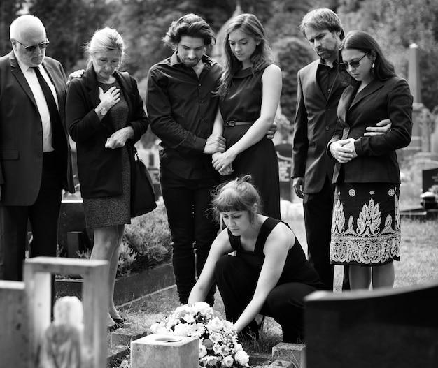 Famille portant des fleurs sur la tombe