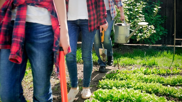 Famille portant des outils de jardinage marchant dans le jardin après un travail acharné.