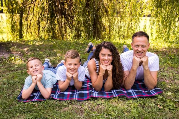 Famille posant sur une couverture de pique-nique
