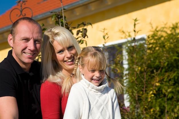 Famille posant devant une maison