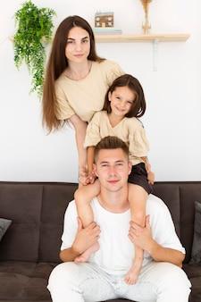 Famille posant ensemble sur un canapé