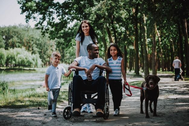 Famille positive dans l'homme du parc en souriant en fauteuil roulant.