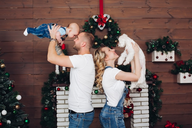 Famille de positivité posant ensemble près de la cheminée et des cadeaux pour noël