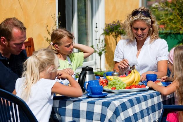 Famille prenant un café dans le jardin