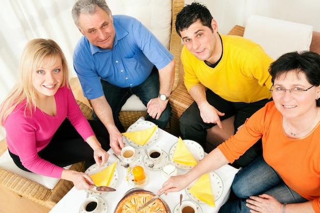 Famille prenant un café et un gâteau ensemble