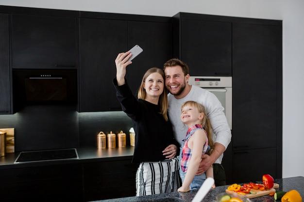 Famille prenant selfie dans la cuisine