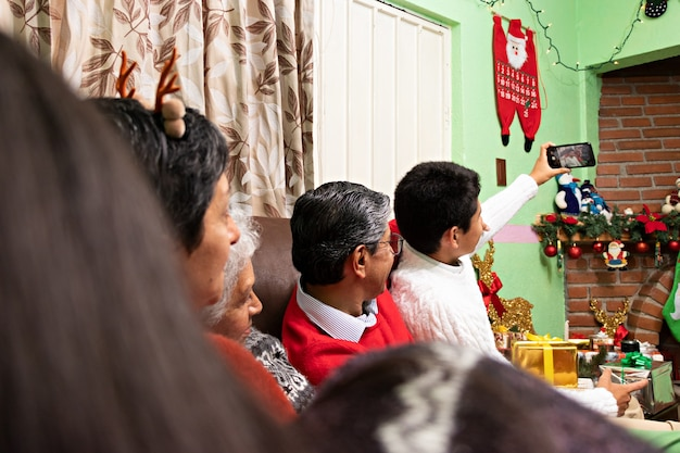 Une famille prenant un selfie ensemble à noël chez les grands-parents
