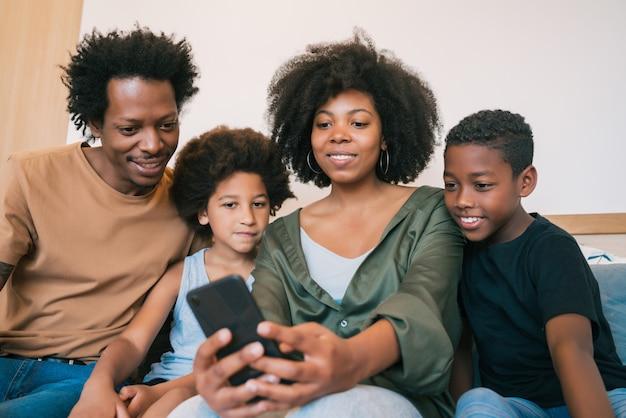 Famille prenant selfie avec téléphone à la maison.