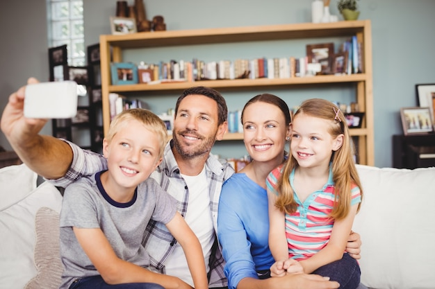 Famille prenant selfie avec téléphone portable sur le canapé à la maison
