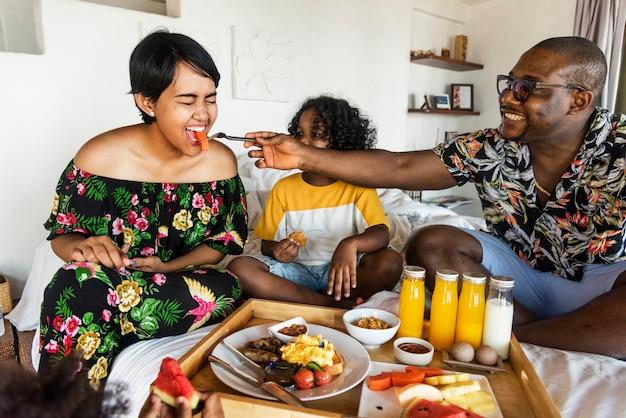 Famille prenant son petit déjeuner au lit