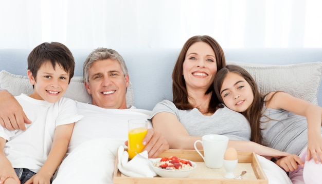 Famille prenant son petit déjeuner dans son lit