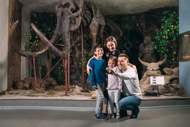 Une famille prend un selfie contre un squelette de mammouth au musée de paléontologie.