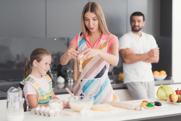 La famille prépare la pâte pour la cuisson.