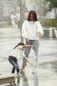 Famille près de la fontaine de la ville. mère avec jauge jouant avec de l'eau.