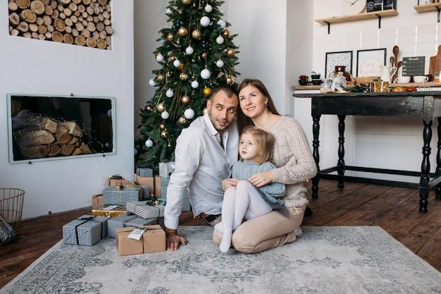 Famille près de sapin de noël et cadeaux